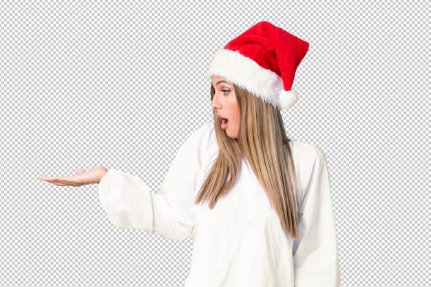 Menina loira com chapéu de natal segurando copyspace imaginário na palma da mão