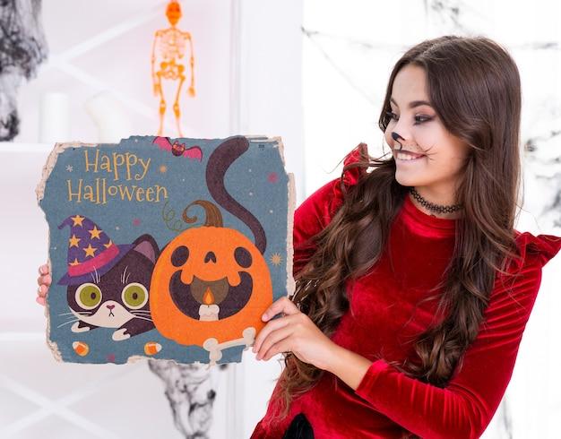 Menina mostrando cartão bonito com gato e abóbora esculpida
