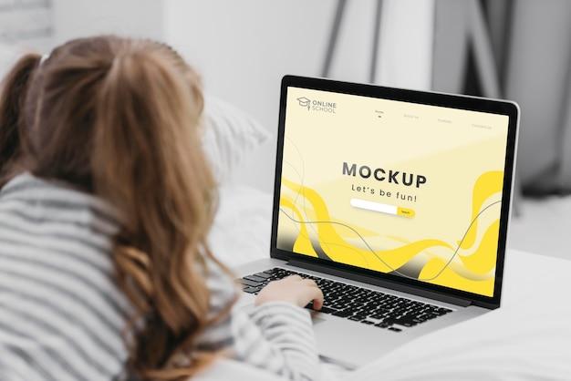 Menina na cama com laptop