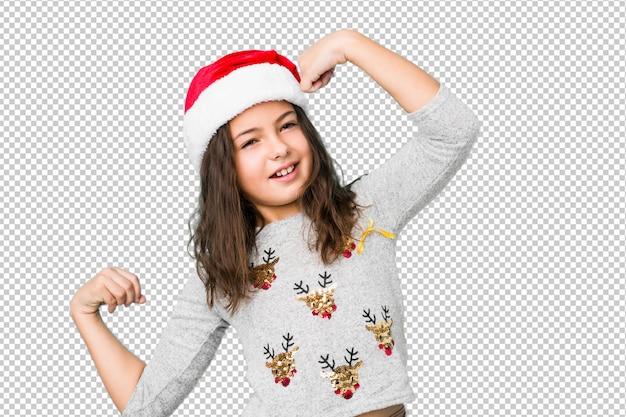 Menina que comemora o dia de natal que levanta o punho após uma vitória, conceito do vencedor.