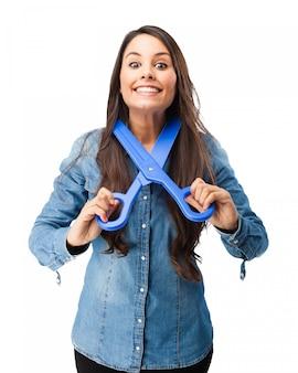 Menina que joga com uma tesoura de plástico