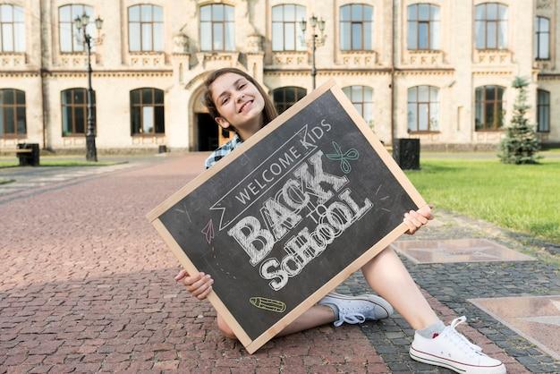 Menina, segurando, costas, para, escola, quadro-negro, mock-up