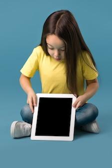 Menina segurando um tablet em branco