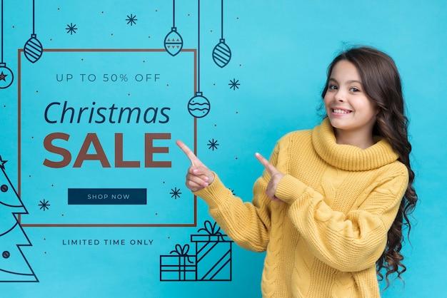 Menina sorridente, apontando para a mensagem com promoções no natal