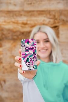 Menina sorridente com capuz mostrando móvel