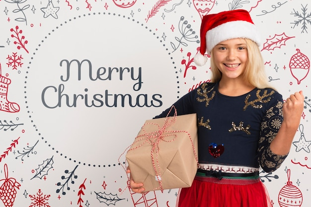 Menina sorridente com chapéu de papai noel segurando o presente