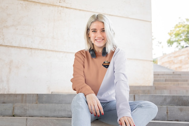 Menina sorridente com fones de ouvido usando capuz