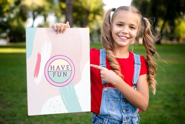 Menina sorridente com mensagem no papel, apontando para ele