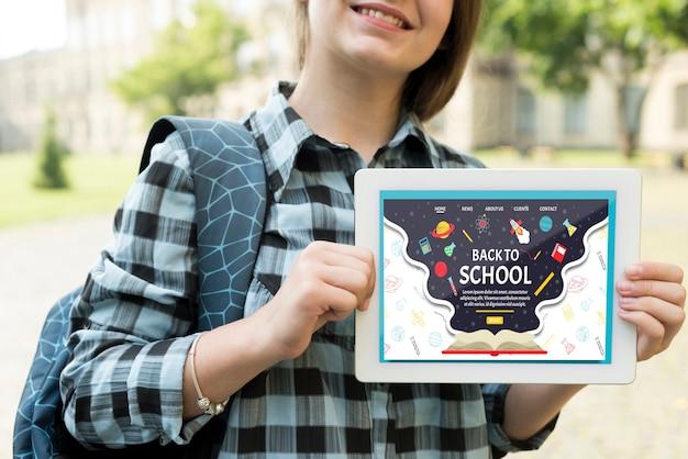 Menina sorridente segurando um tablet mock-up