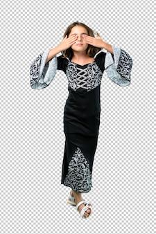 Menina vestida como um vampiro para as férias de halloween cobrindo os olhos pelas mãos