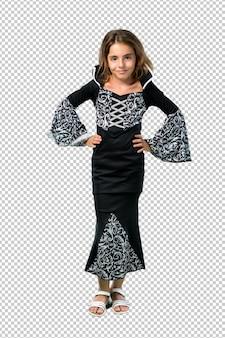 Menina vestida como um vampiro para as férias de halloween, posando com os braços no quadril
