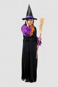 Menina vestida como uma bruxa para as férias de halloween cobrindo ambas as orelhas com as mãos