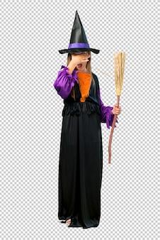 Menina vestida como uma bruxa para as férias de halloween cobrindo os olhos pelas mãos