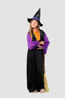 Menina vestida como uma bruxa para as férias de halloween ficar e olhando para cima