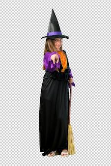 Menina vestida como uma bruxa para feriados de halloween aponta o dedo para você