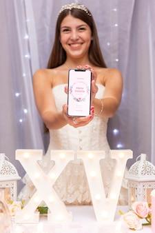 Menina vestindo uma tiara e segurando uma maquete de aniversário de 15 anos