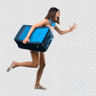 Menina viajando com sua mala correndo rápido