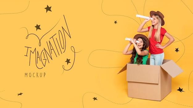 Meninas brincando em caixa de papelão