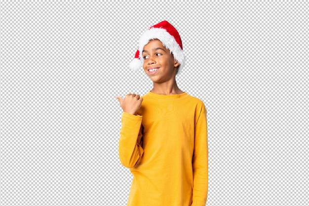 Menino afro-americano com chapéu de natal apontando para o lado para apresentar um produto