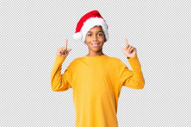 Menino afro-americano com chapéu de natal apontando uma ótima idéia