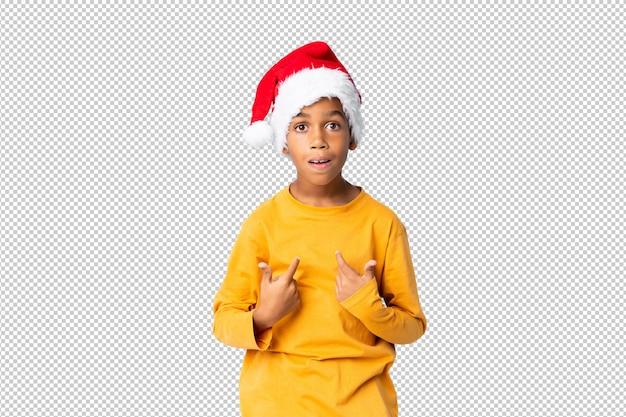 Menino afro-americano com chapéu de natal com expressão facial de surpresa