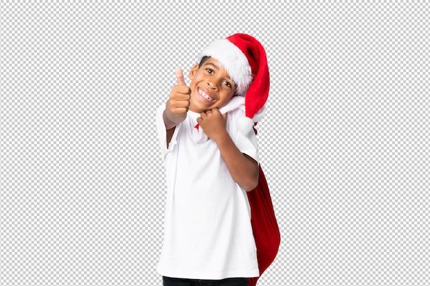 Menino afro-americano com chapéu de natal e levar uma sacola com presentes e com o polegar para cima