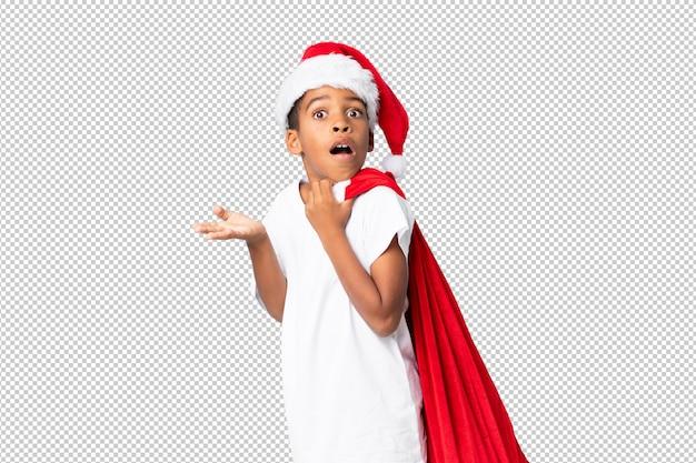 Menino afro-americano com chapéu de natal e levar uma sacola com presentes e fazendo o gesto de surpresa