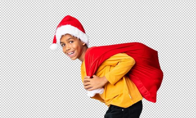 Menino afro-americano com chapéu de natal e levar uma sacola com presentes