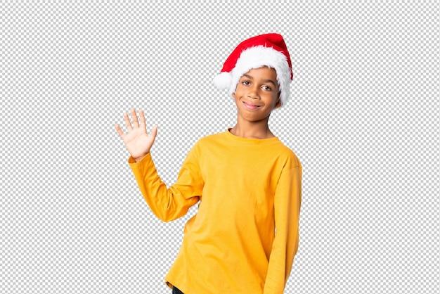 Menino afro-americano com chapéu de natal saudando com a mão com expressão feliz