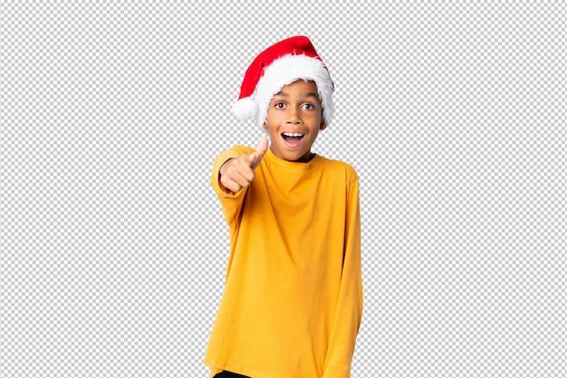 Menino afro-americano com chapéu de natal surpreso e apontando a frente