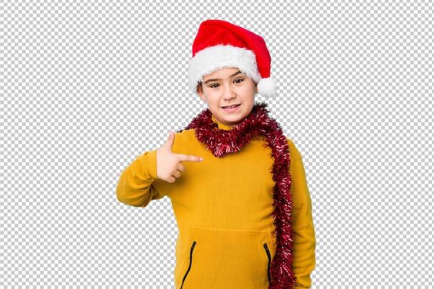Menino comemorando o dia de natal, vestindo uma pessoa isolada de chapéu de papai noel, apontando à mão para um espaço de cópia de camisa, orgulhoso e confiante