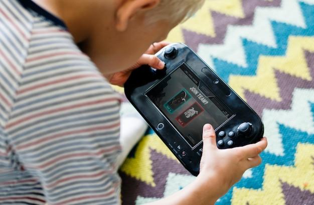 Menino jovem, tocando, um, portátil, videogame