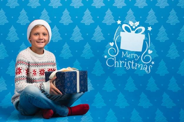 Menino vestido de presente de abertura de camisola temática de natal