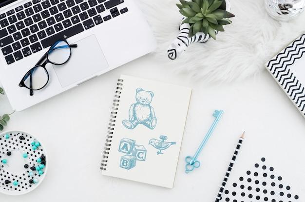 Mesa com maquete de notebook e óculos
