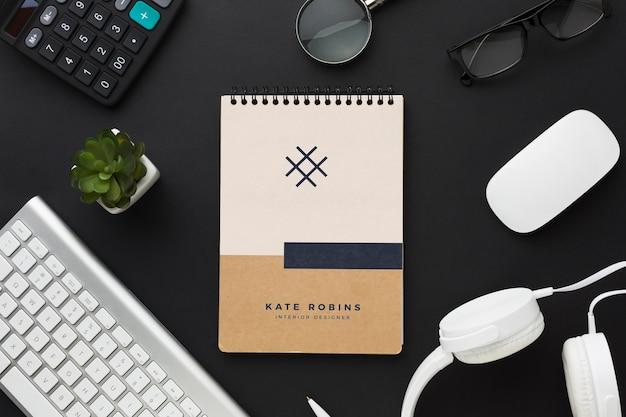 Mesa de escritório com teclado, fones de ouvido e maquete de notebook