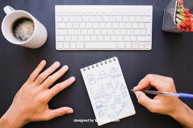 Mesa de escritório e desenho de mãos com caneta no caderno