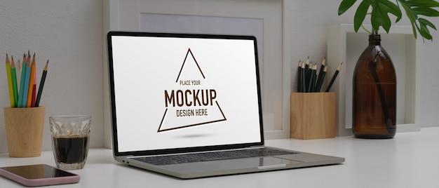 Mesa de escritório em casa com maquete de laptop, smartphone, artigos de papelaria e decorações