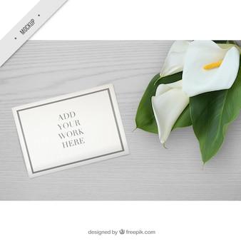 Mesa de madeira com flores e maquete de papel para mostrar o seu trabalho