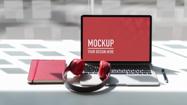 Mesa de trabalho com maquete de laptop, fone de ouvido e notebook
