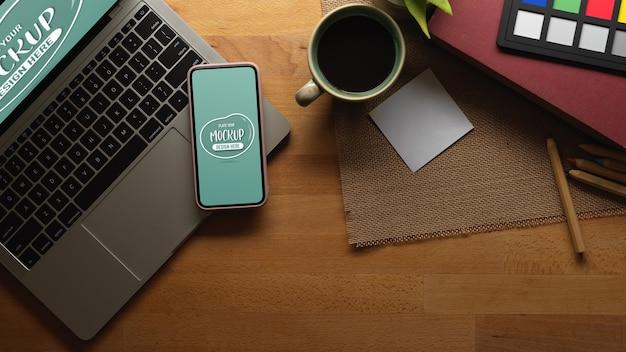 Mesa de trabalho com maquete de smartphone, laptop e café