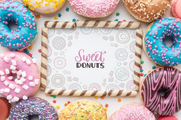 Mistura de donuts coloridos e paus de bolacha quadro mock-up