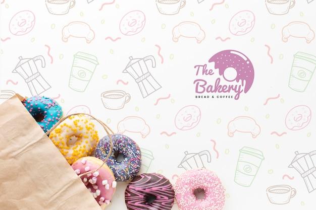 Mistura de donuts coloridos em saco de papel com maquete