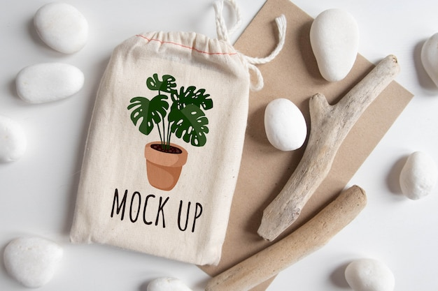 Mock-se de saco de algodão de baralho de tarô com envelope de textura papel artesanal marrom e vara rústica na mesa branca