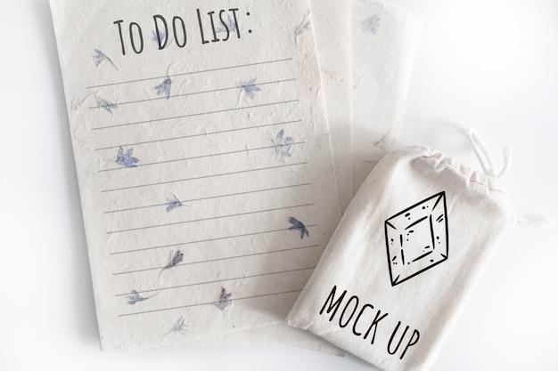 Mock-se do saco de algodão de baralho de tarô com folhas de papel de textura no fundo branco