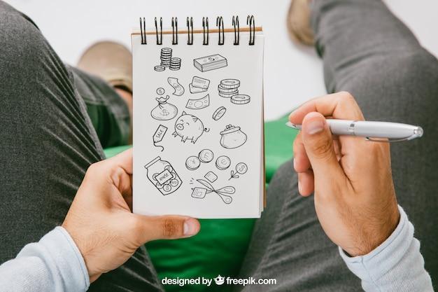 Mock up com as mãos desenhando no caderno