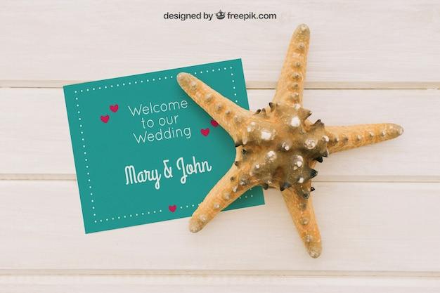 Mock up com convite de casamento e estrela do mar