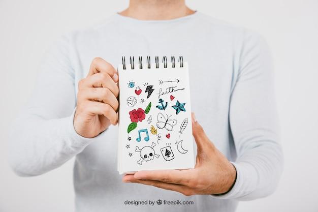 Mock up design com as mãos segurando notebook