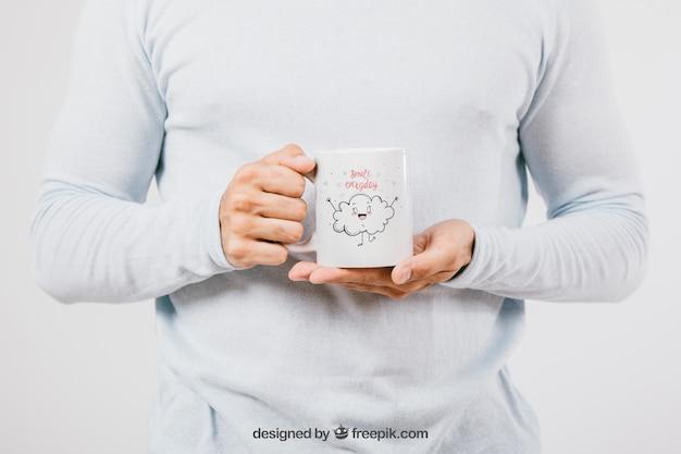 Mock up design com as mãos segurando uma caneca de café