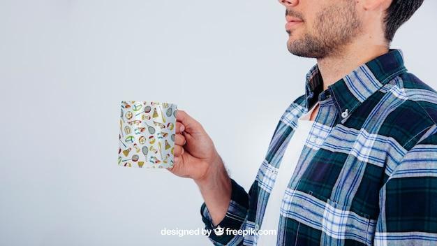 Mock up design com jovem homem segurando caneca de café