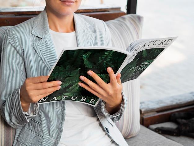 Mock-up mulher lendo revista sobre a natureza